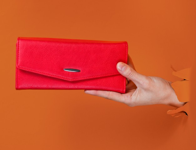 female-hand-holding-red-wallet-through-torn-orange-paper-minimalistic-creative-fashion-concept_175682-13337