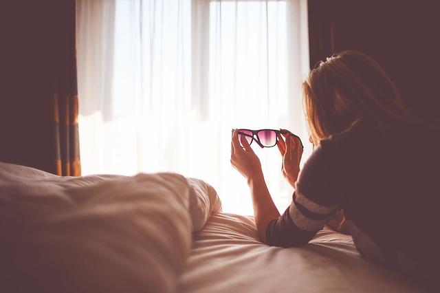 Žena, ktorá drží slnečné okuliare v rukách a leží na posteli.jpg