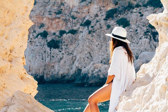 Žena v bielom klobúku sediaca na skale pri mori.jpg