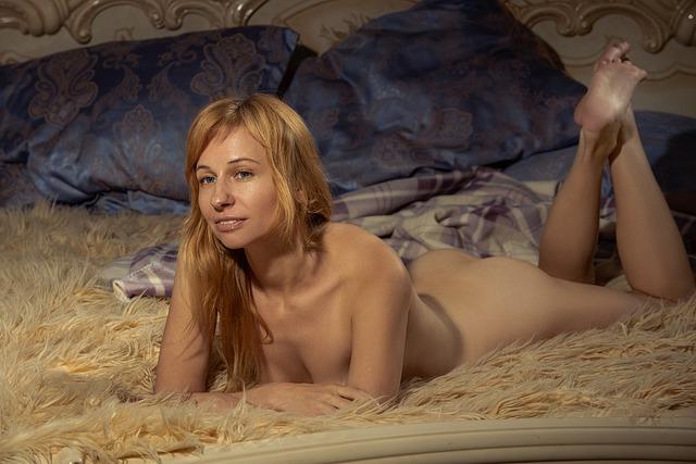 Nahá žena s blond vlasmi leží na bruchu na posteli.jpg