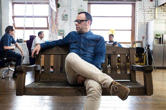 Muž sedí na drevenej hojdačke s prekríženými nohami.jpg