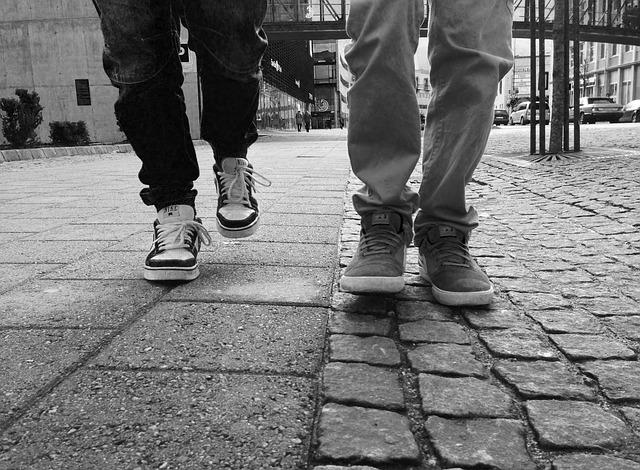 Dvaja ľudia kráčajú po chodníku vedľa seba.jpg